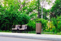 Pair of wooden park chairs and trashcan in green summer park royalty free stock photo