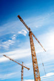Two Industrial Cranes Working on Construction Site Stock Photography