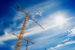 Two Industrial Cranes Working on Construction Site. Two Yellow Industrial Cranes Working on Construction Site Against Blue Sky Stock Photos