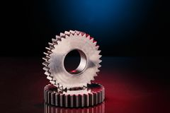 Two industrial metal gears on glossy surface. Composition of two shiny futuristic metal gears for heavy machinery and spare-parts conceptual designs with Stock Images