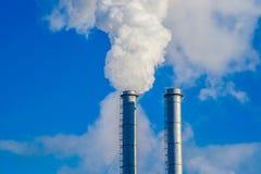 Two industrial metallic chimneys emitting the white smoke Stock Photography
