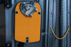 Orange damper actuator installed on the industrial ventilation unit body, front view. Two industrial orange damper actuators installed on the air handling unit stock image