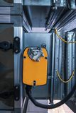 Orange damper actuator installed on the industrial ventilation unit body, front view. Two industrial orange damper actuators installed on the air handling unit stock photos