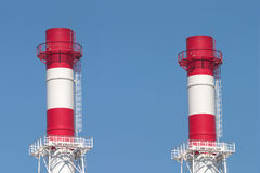 Two industrial smoke pipes over blue sky Royalty Free Stock Photo