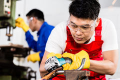Two industrial workers in Asian metal factory. With electrical grinding tool and power drill machine Royalty Free Stock Photos