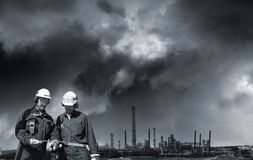 Two industry workers and distant oil refinery Royalty Free Stock Photo