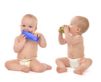 Two infant child baby toddlers sitting eating blue toy and green. Two infant child baby toddlers sitting and eating blue toy brick and green apple in hand Royalty Free Stock Photography