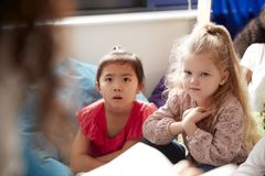 Two infant school girls sitting on bean bags in a comfortable corner of the classroom listening to their teacher reading a story,. View over teacher�s stock photography
