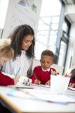 Two infant school kids and their female teacher sitting at table in a classroom drawing, low angle royalty free stock photography