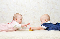 Two infants with apple Stock Images