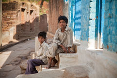 Two innocent  indian villager child. Two innocent  indian child sitting on steps in village street Royalty Free Stock Photo