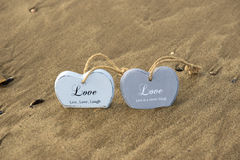 Two inscribed wooden love hearts in the quick sand Royalty Free Stock Photography