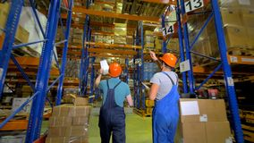 Two inspectors walk through a giant warehouse. Two workers walk in a large warehouse with numbers on storage racks stock footage