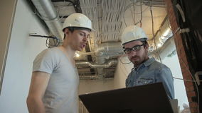 Two installers of the ventilation system look at the laptop. People with an unshaven face hold a computer in their hands stock footage