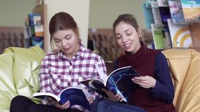 Two interested female students in library talking about the articles from books. Two interested female students sitting in library together and talking about the stock video