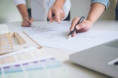 Two interior design or graphic designer at work on project of ar. Chitecture drawing with work tools and color swatches, colour chart, color samples for Royalty Free Stock Images