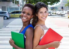 Two international female students back to back Stock Photos