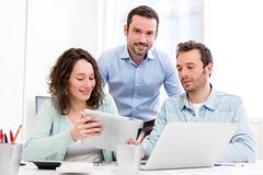 Two interns working together assisted by their course supervisor Royalty Free Stock Photos