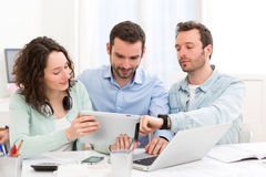 Two interns working together assisted by their course supervisor Royalty Free Stock Photo