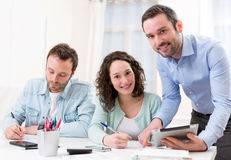 Two interns working together assisted by their course supervisor Stock Photos