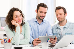 Two interns working together assisted by their course supervisor Royalty Free Stock Photography