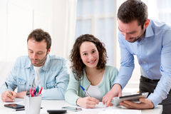 Two interns working together assisted by their course supervisor Royalty Free Stock Image