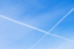Two intersecting Condensation tracks of airplanes on clear blue sky. With place for your text, for background use. Stock Images