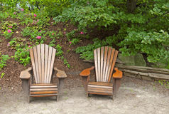 Two inviting wooden Lawn chairs Royalty Free Stock Images