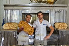 Two Iranian bakers show flatbread barbari inside bakery, Kashan, Iran. royalty free stock photo