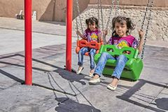 Two Iranian little girls twins on a swing, Kashan, Iran. Kashan, Iran - April 26, 2017: Two unknown little girls twins, about 5 years old, are swinging on a stock photography