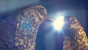 Two iron dove. Two doves forged from iron in the background shines the spotlight stock photos