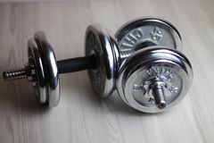 Two iron dumbbells on a wooden background stock photography