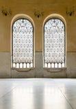 Two iron ornate windows over yellow stone wall Royalty Free Stock Photo