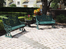 Two iron park benches by a patio Stock Images
