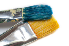 Two isolated blue yellow used painter brush. Two isolated blue and yellow used paintbrush on white background Royalty Free Stock Image