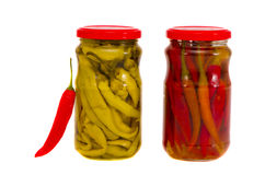 Two isolated glass jars with red and green peppers Royalty Free Stock Photography