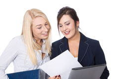 Two isolated young smiling businesswoman looking at a white pape Royalty Free Stock Photos
