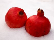 Two isolates objects red pomegranate fruit on white snow outdoors in winter in natural light. Vitamins and minerals, healthy food in winter Stock Photos