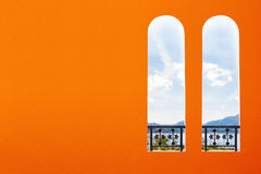Two Italian arched windows on orange wall Stock Images