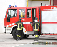 Two Italians firefighters descend from fire trucks Stock Photos