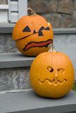 Two Jack-o-lanterns. Two spooky Halloween Jack-o-lanterns sit on a slate stairs royalty free stock image