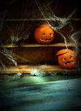 Two Jack o Lanterns Carved from Oranges on Shelf. Two Halloween Jack o Lanterns Carved from Oranges and Spiderwebs with Spiders on Shelves Blurred in Background Royalty Free Stock Photo