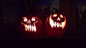 Smiling Jack O`Lanterns by the Window. Two Jack O`Lanterns sit by the window with fiery smiles shining out in the dark. They await eager trick or treaters to royalty free stock photos