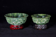 Two Jade bowls with wooden base isolated on dark background Stock Photos