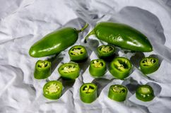 Two jalapeno peppers and some chopped up showing it seeds. The jalapeño /ˌhɑːləˈpeɪnjoʊ, ˌhæl-, -ˈpiːnoʊ/;[1] Spanish: [xalaˈpeɲo] About this stock photo