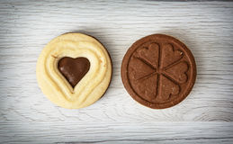 Two jam biscuits in the shape of heart and clover leaf on the wo Stock Image