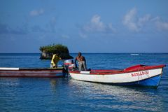 Jamaican fishermen in traditional boats at Blue Lagoon, Jamaica Stock Images
