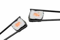 Sushi Roll in The Chopsticks. Typical Japanese Food. Two japan sushi roll in the chopsticks over white background Stock Images