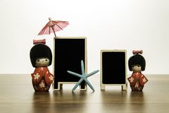 Two Japanese dolls with two blank black board with blue star fish and red umbrella Royalty Free Stock Image