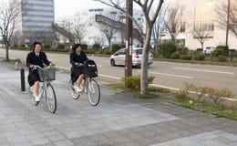 Two Japanese school girl riding a bicycle. Kanazawa, Japan - March 30th, 2017: Two school girls riding a bicycle at Ishikawa-ken, Kanazawa-shi, Tomizu, 1 Chome royalty free stock photos